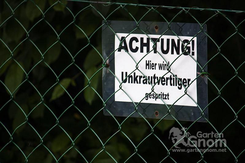 Schild mit Aufschrift: Achtung! Hier wird Unkrautvertilger gespr